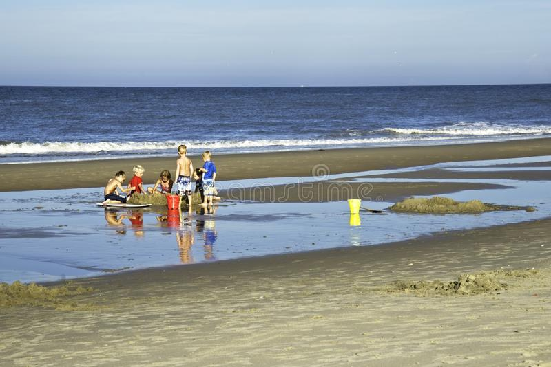 开掘在弗吉尼亚海滩弗吉尼亚` s海滩的沙子的孩子 免版税图库摄影