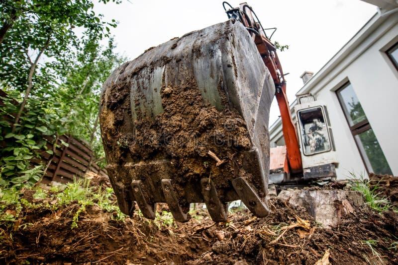 开掘在建造场所的工业耐用挖掘机 瓢和金属桶特写镜头  免版税库存照片
