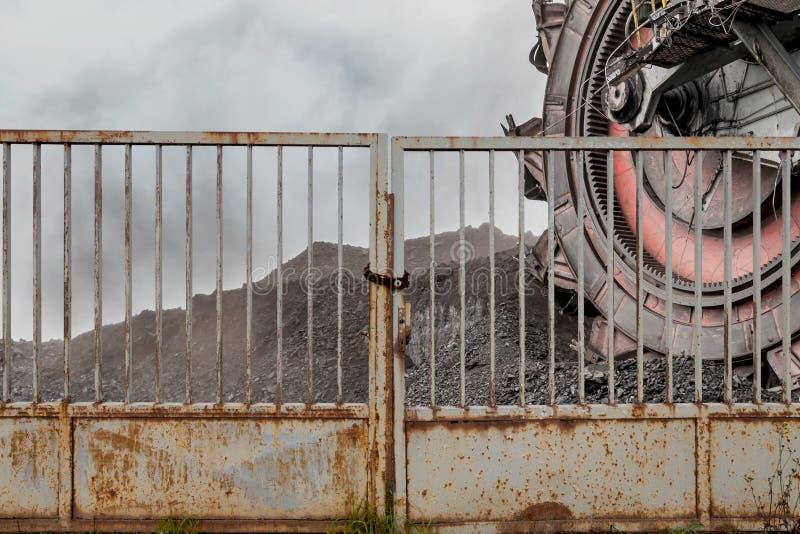 开掘的褐煤巨型戽头转轮挖土机在铁门后 免版税库存照片