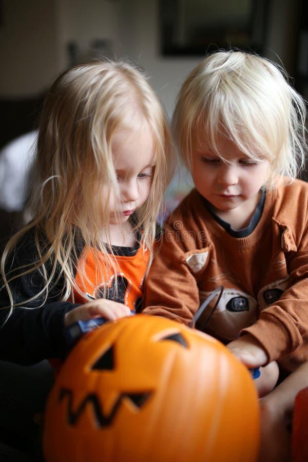 开掘通过万圣节糖果的南瓜桶的两个女孩孩子 库存照片