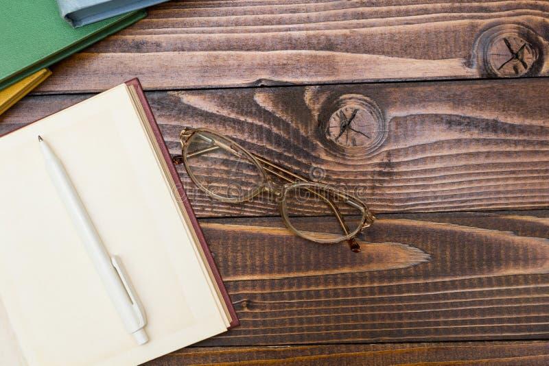 开放书、笔和玻璃在一张木桌上 图库摄影