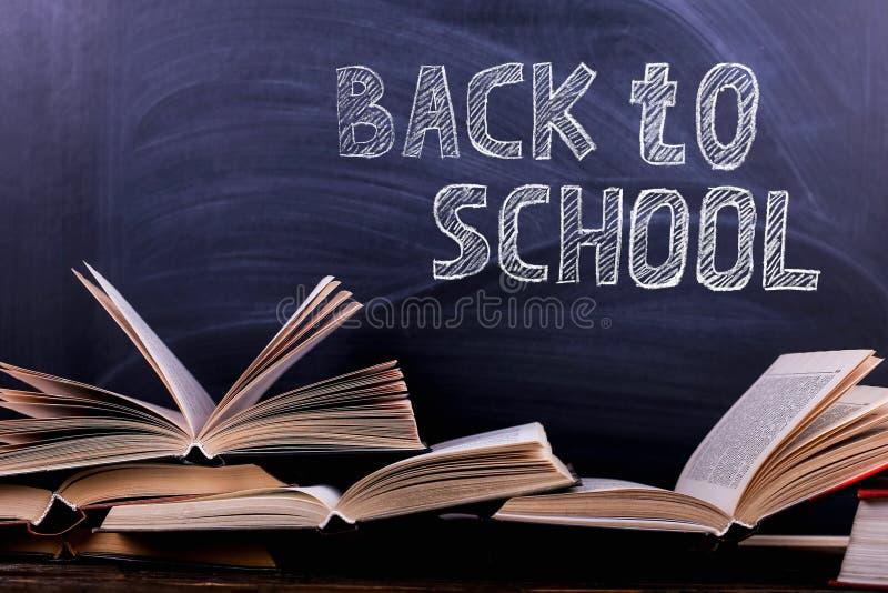 开放书是在书桌上的堆,以粉笔板为背景 困难的家庭作业在学校,知识山  免版税库存照片