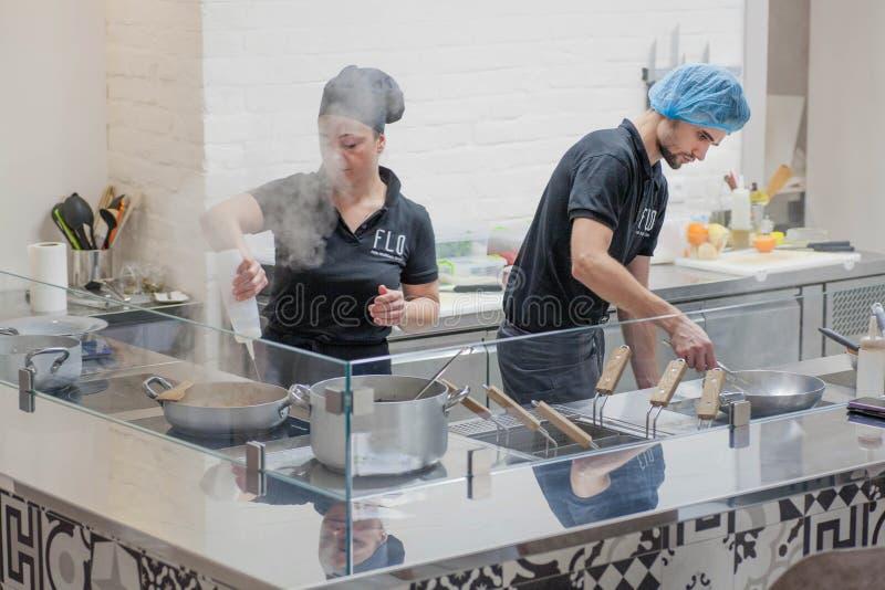 开放厨房,在烹调食物的厨师附近的蒸汽的工作者在现代餐馆 库存图片