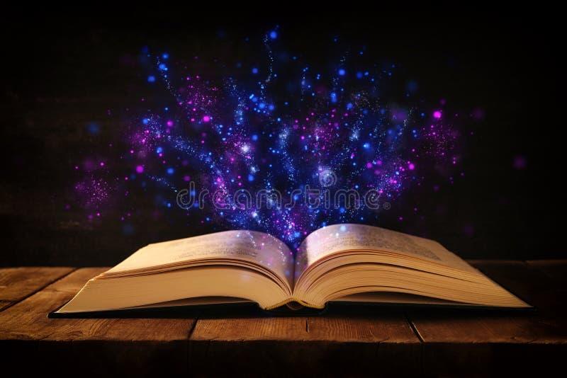 开放古色古香的书的图象在木桌上的与闪烁覆盖物 免版税库存照片