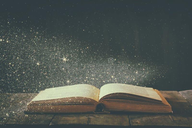 开放古色古香的书的抽象图象在木桌上的 选择聚焦 减速火箭过滤和定调子与闪烁覆盖物 免版税图库摄影