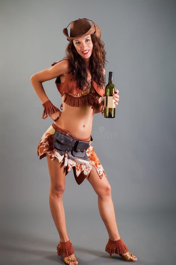 开放牛仔舞蹈服装帽子姿势的女孩与瓶 库存图片