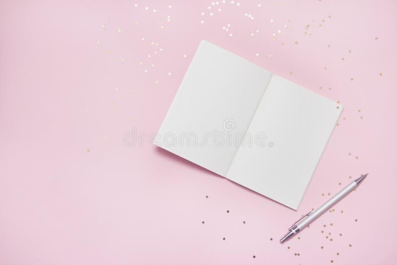 开放空的笔记本顶视图有星五彩纸屑的在粉红彩笔五颜六色的背景 库存图片