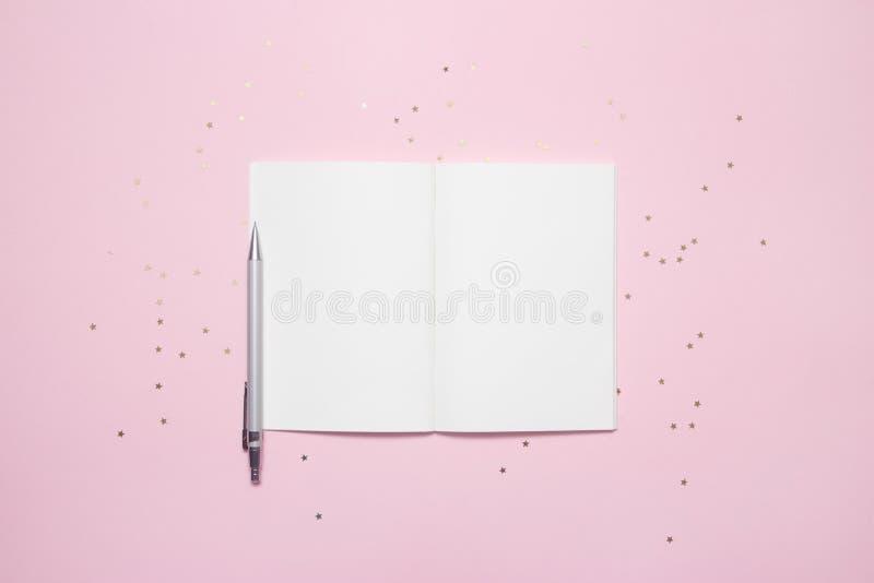 开放空的笔记本顶视图有星五彩纸屑的在粉红彩笔五颜六色的背景 图库摄影