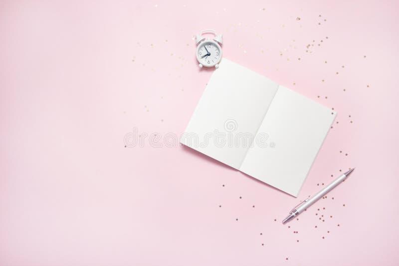 开放空的笔记本顶视图有葡萄酒闹钟的在粉红彩笔五颜六色的背景 免版税图库摄影