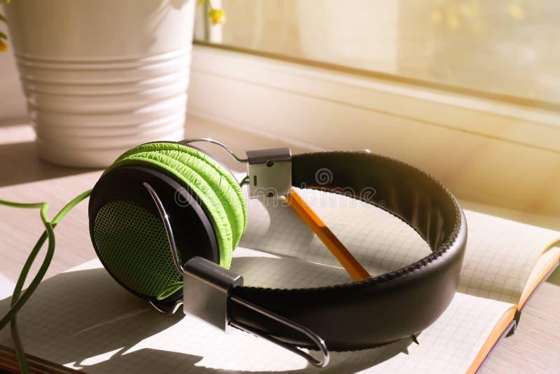 开放笔记本和耳机在窗台 免版税库存照片