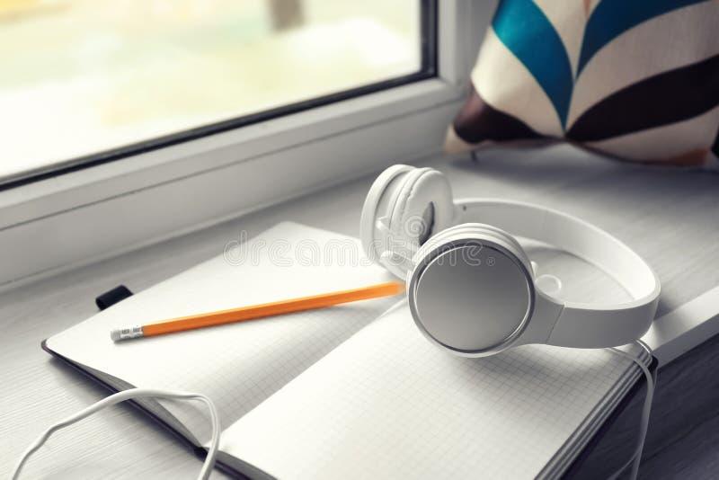 开放笔记本和耳机在窗台 库存图片