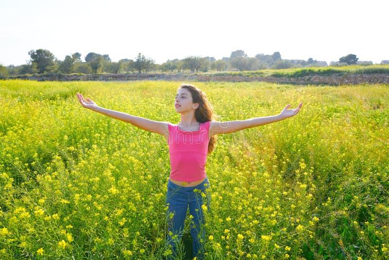 开放胳膊愉快的青少年的女孩在春天草甸 免版税库存图片