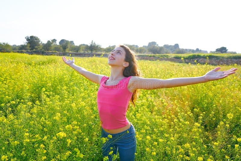 开放胳膊愉快的青少年的女孩在春天草甸 库存图片