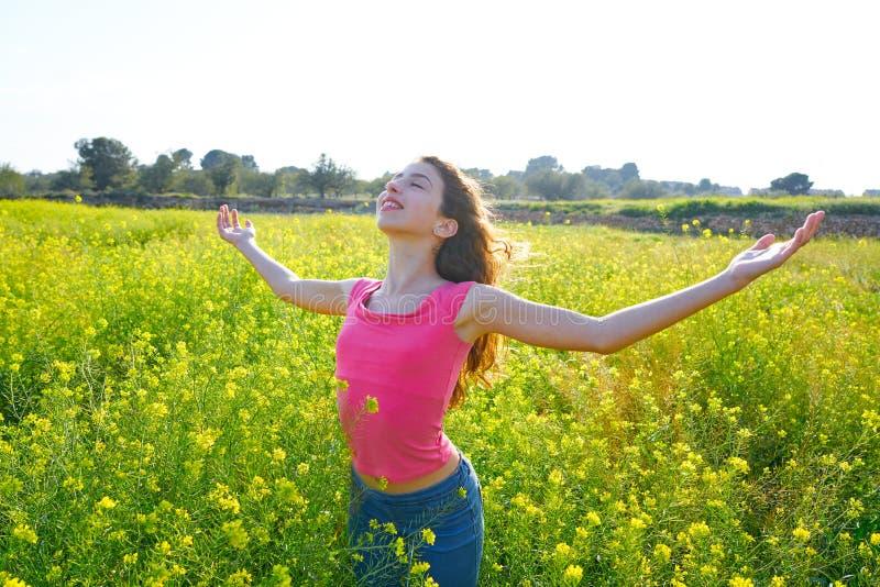 开放胳膊愉快的青少年的女孩在春天草甸 免版税库存照片