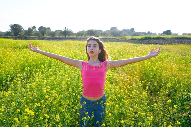 开放胳膊愉快的青少年的女孩在春天草甸 免版税图库摄影