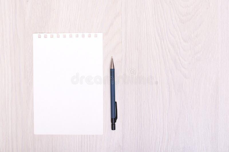 开放螺旋空白的笔记本顶视图有铅笔的在木书桌背景 图库摄影
