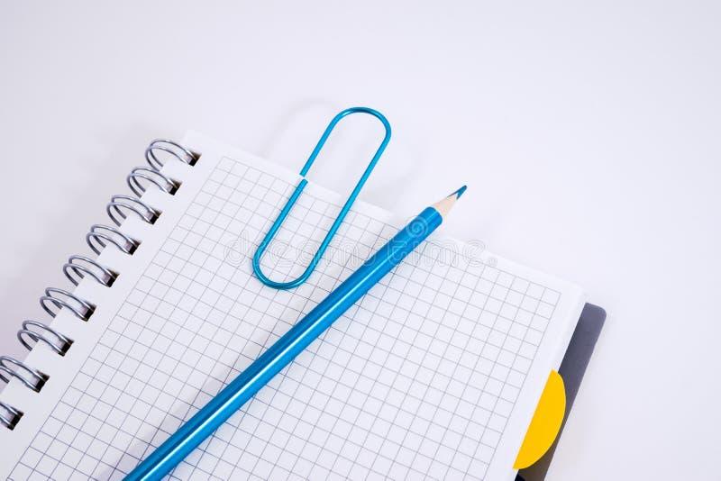 开放螺旋空白的笔记本顶视图有铅笔的在白色书桌背景 库存图片