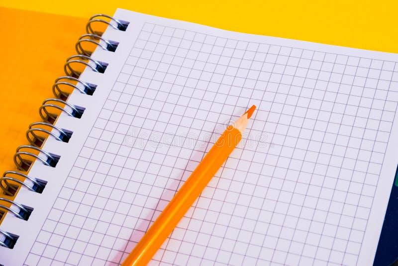 开放螺旋空白的笔记本顶视图有铅笔的在黄色书桌背景 免版税库存图片