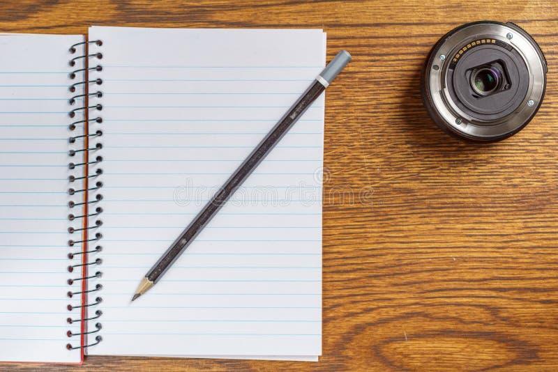 开放螺纹笔记本顶视图有黑铅笔和摄象机镜头的在书桌背景 库存照片