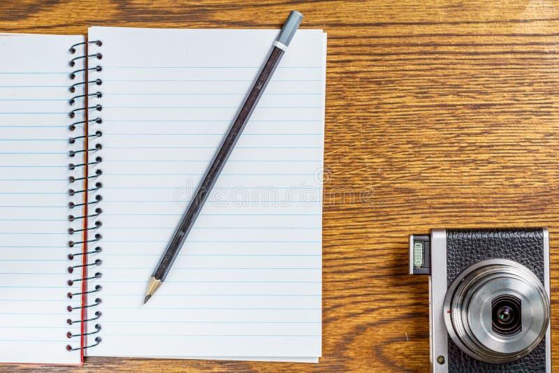 开放螺纹笔记本顶视图有黑铅笔和照片照相机的在书桌背景 免版税图库摄影