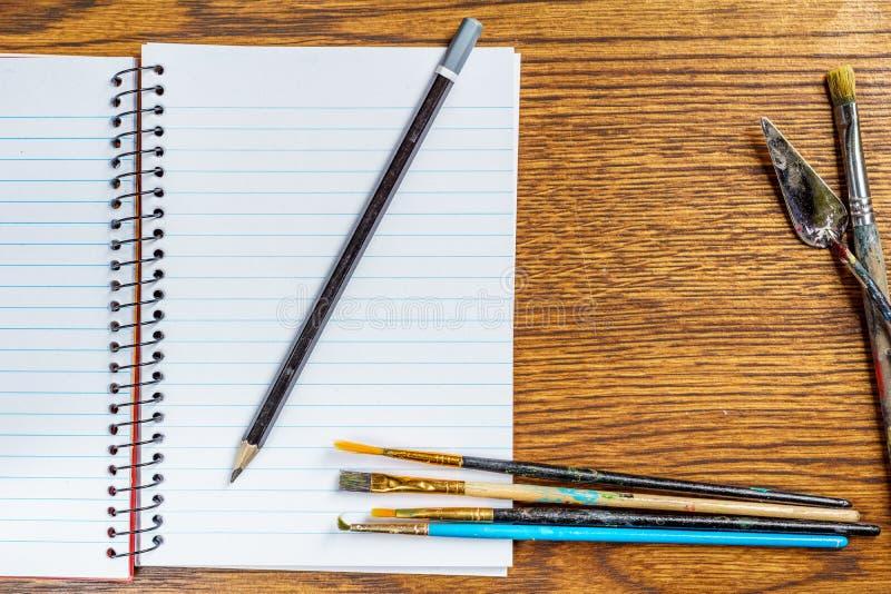 开放螺纹笔记本顶视图有黑铅笔和画笔的在书桌背景 免版税库存图片