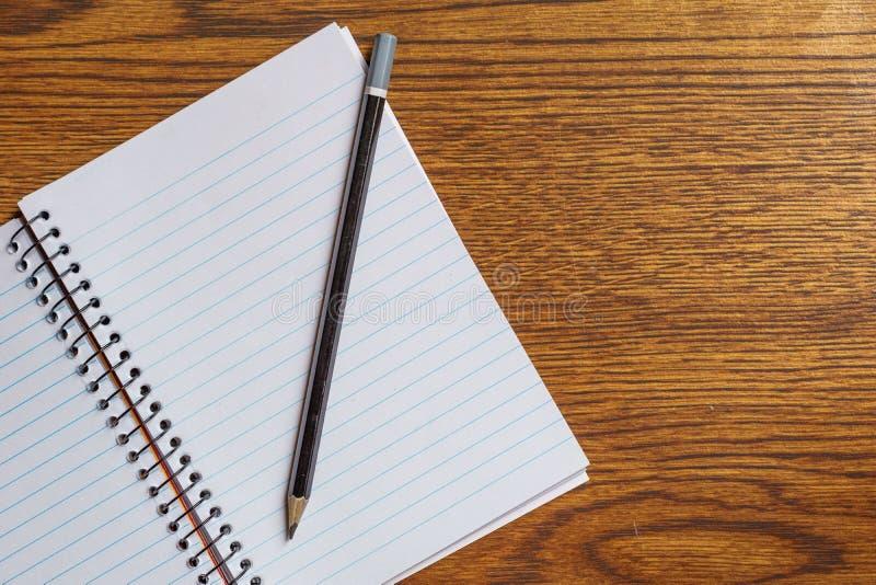 开放螺纹笔记本顶视图有黑铅笔的在书桌背景 免版税库存图片