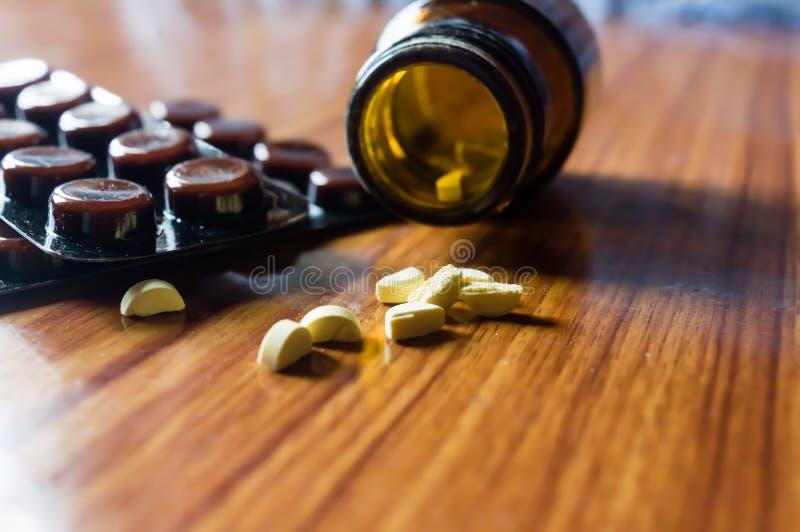 开放透明玻璃瓶的关闭有医学药片的或片剂在木桌背景的天线罩包装 药房治疗和 库存照片