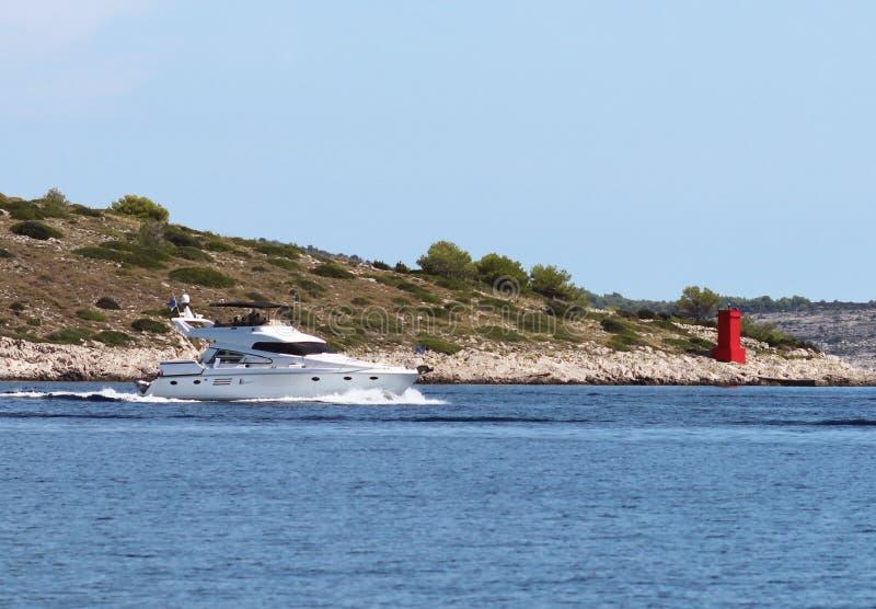 开汽车运行沿沿岸的蓝色海的游艇 地中海地区亚得里亚海  克罗地亚国家的达尔马希亚地区 图库摄影