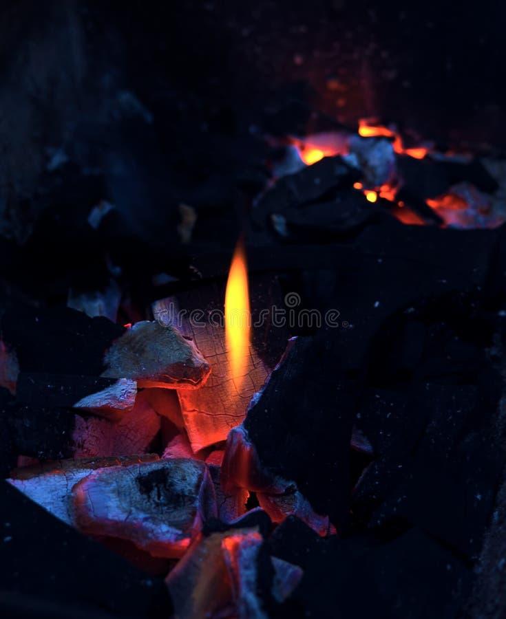 开火烤肉背景:与热的火焰关闭的灼烧的木炭 蓝色桔子 阵营火,格栅,传统火炉 免版税库存照片