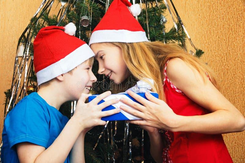 开玩笑地设法少年的兄弟姐妹互相夺走` s圣诞节礼物 免版税库存图片