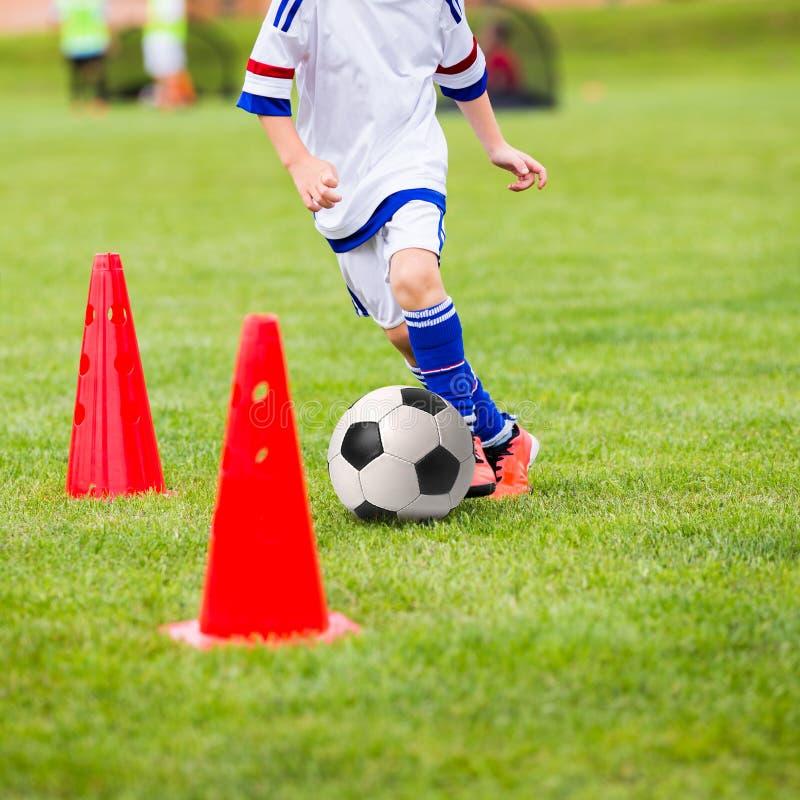 开玩笑踢足球 训练孩子的橄榄球会议 男孩训练与足球和系船柱在领域 免版税库存图片