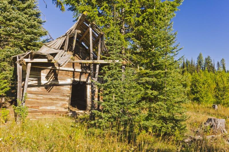 离开的原木小屋在蓝天下 免版税库存图片