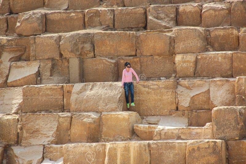 开罗,埃及- 2015年4月22日,女孩坐埃及金字塔的古老石头在吉萨棉, 2015年4月22日在开罗, EGY 库存照片