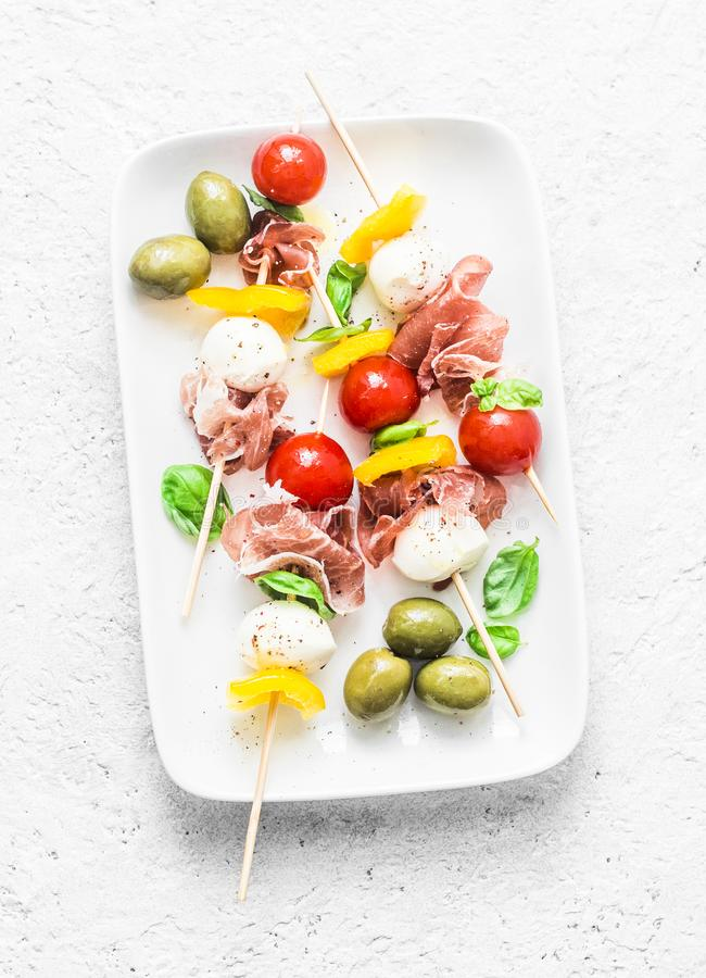 开胃小菜串 喝酒的地中海开胃菜-熏火腿,甜椒,西红柿,在串的无盐干酪乳酪 熟食店 免版税图库摄影