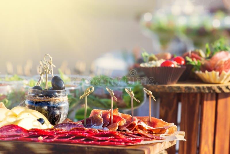 开胃小菜承办的盛肉盘用蒜味咸腊肠和乳酪在木背景synny天,拷贝空间 免版税图库摄影