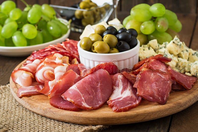 开胃小菜承办酒席盛肉盘用烟肉,生涩,蒜味咸腊肠、乳酪和葡萄 库存照片