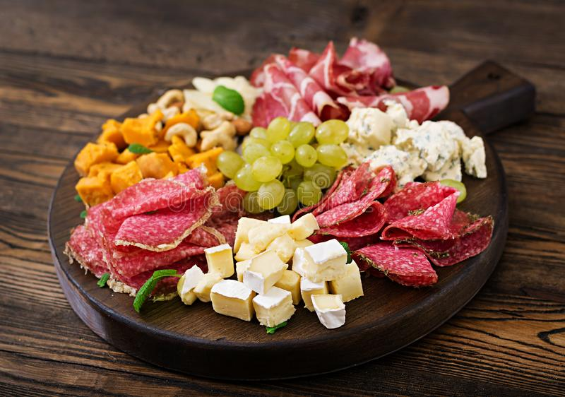 开胃小菜承办酒席盛肉盘用烟肉,生涩,香肠、青纹干酪和葡萄 免版税库存图片