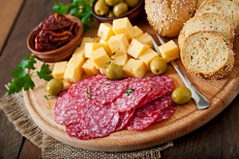 开胃小菜承办酒席盛肉盘用蒜味咸腊肠和乳酪 免版税库存照片