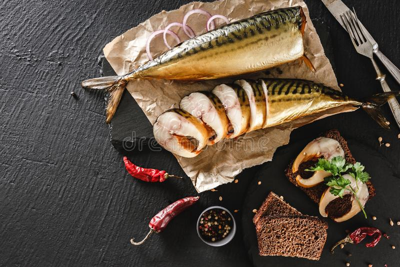 开胃熏制的鱼用香料、利器、胡椒和面包在工艺纸在黑暗的石背景 与抽烟的三明治 库存照片
