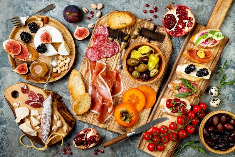 开胃菜制表与意大利开胃小菜快餐 Brushetta或地道传统西班牙塔帕纤维布设置了,乳酪品种委员会 免版税库存图片