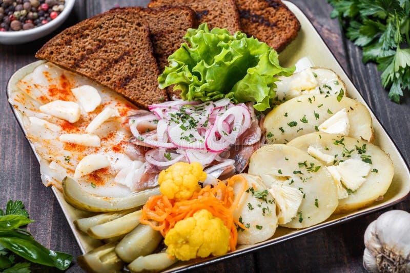 开胃菜盛肉盘、被烘烤的土豆、可口被切的猪肉油脂用香料,被切的熏制的鱼用葱,腌汁和面包 库存图片
