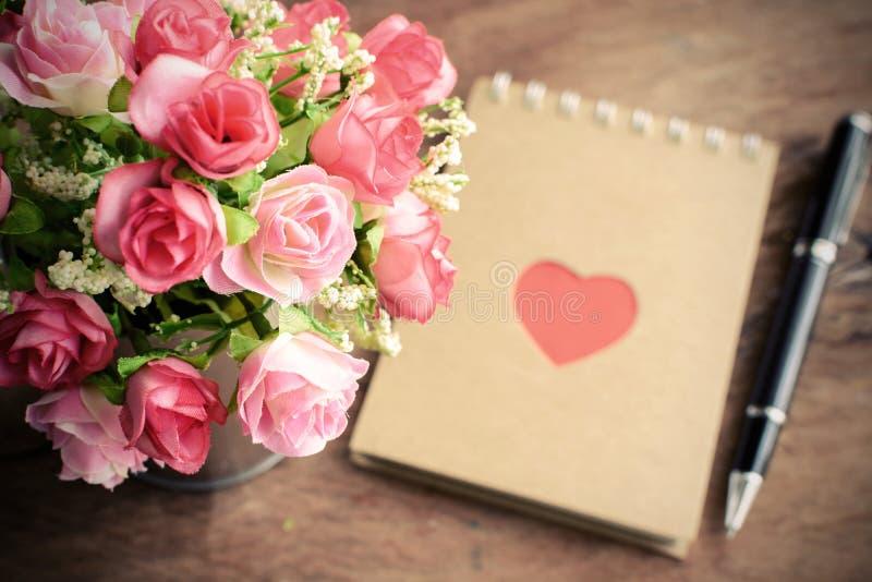 开花与空白的笔记薄和笔在老木背景 免版税图库摄影