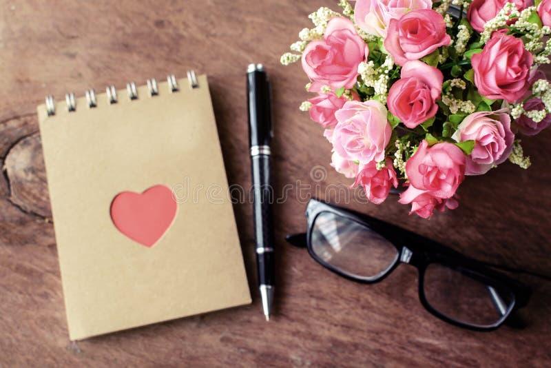 开花与空白的笔记薄和笔在老木背景 免版税库存照片