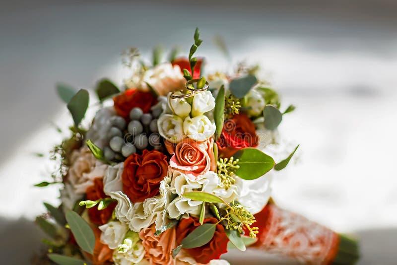 开花与金子新娘婚戒的婚礼花束  库存照片