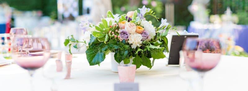 开花假日和结婚宴会的桌装饰 表为假日、事件、党或者结婚宴会设置了室外休息的 免版税图库摄影