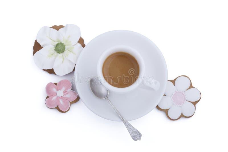 开花形状的姜饼曲奇饼和咖啡与匙子的在白色背景 免版税库存图片