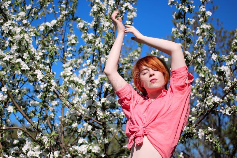 开花的树背景的红发女孩,女孩向上拉扯她的手,在开花的春天时尚女孩室外画象 免版税库存图片