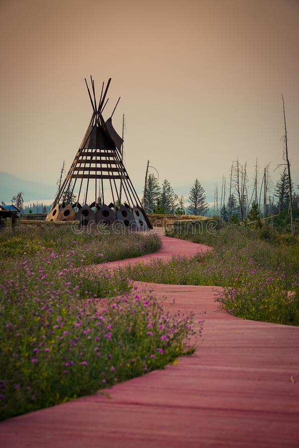 开花的红土走道导致一个美丽的金属圆锥形帐蓬 免版税库存照片