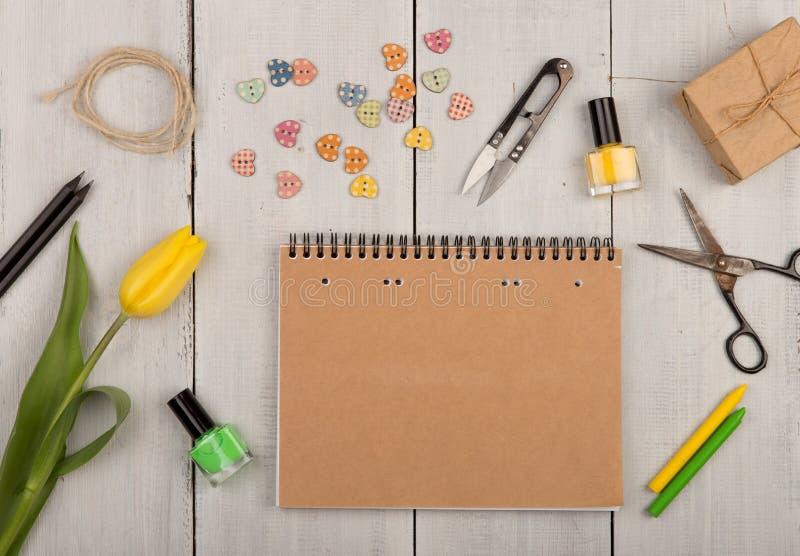 开花郁金香、空白的笔记本、剪刀、指甲油和按钮以心脏的形式 图库摄影