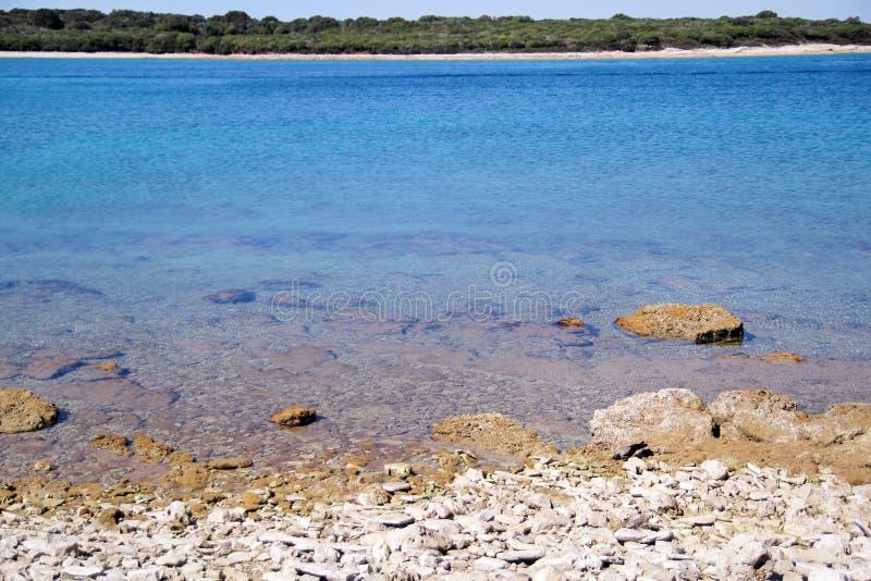 异乎寻常的多岩石的海滩、热带蓝色地中海有波浪的和海泡沫 r 免版税库存照片